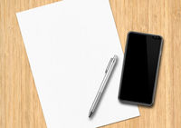 Sheet of paper, pen and smartphone on a wooden desk