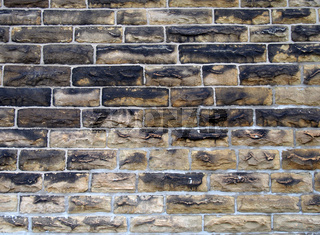 a full frame image of a large old dark stone wall made of large sandstone blocks