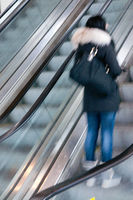 Young teenager woman in movement standing alone in an urban up moving escalator leaving  the subway station traveling upstairs to the city mall