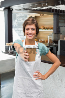 Pretty barista smiling at camera holding disposable cup