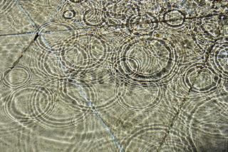 Wasseroberflaeche mit Regentropfen
