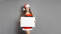 young woman in santa claus christmas costume presenting blank sign with copy space