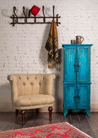 Classic beige armchair, vintage turquoise cupboard, and wall hanger with ornate scarf on bricks wall
