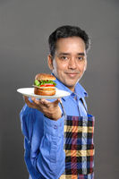 Indian Male Chef with a Burger in Hand on Grey Background