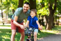 father teaching little son to ride bicycle at park