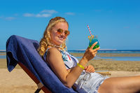 Young woman drinks cocktail on beach bed