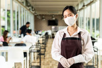Portrait of waitress with facemask in New normal restaurant background