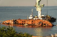 Rescue wrecked oil tanker Delfi in Odessa, Ukraine 26 August 2020, near Black Sea coast. Marine Crane lift wreck Delphi into sea. Old rusty ship lie on side aground, tug pulls ship out after accident