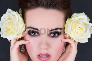 Junge Frau hält zwei gelbe Rosen seitlich neben ih