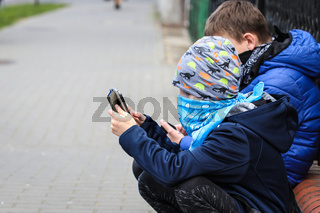 Two boys with covered face play on smartphones