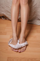 unrecognizable young woman undressing dropping white thong panties on bedroom floor