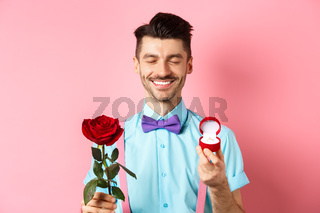 Valentines day. Cute boyfriend making wedding proposal, showing engagement ring in small box and red rose, express love, standing over pink background