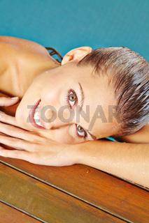 Glückliche Frau am Beckenrand im Schwimmbad