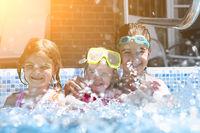 Three cute girls playing in swimming pool
