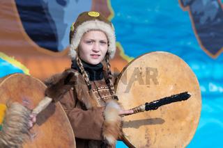Girl dancing with tambourine in tradition clothing aborigine people Kamchatka Peninsula. Celebration Koryak national ritual holiday Day of Seal - Hololo. Kamchatka, Russia - Nov 4, 2018