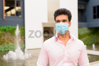 Young Indian businessman with mask thinking in the city outdoors