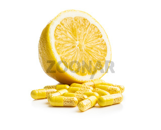 Vitamin capsules. Vitamin C pills and yellow lemon.