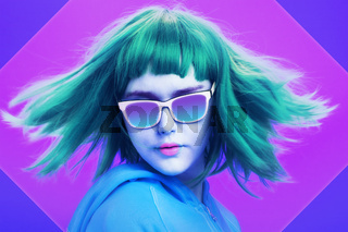 Art collage with alternative funky girl with blue hair on a bright blue purple background. Close up fashion portrait young beautiful woman in hoodie and glasses. Unusual youth fashion concept.
