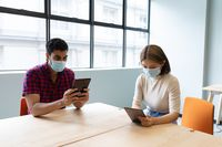 Diverse male and female business colleague wearing face masks using tablets