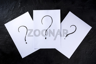 Question marks, written in ink on a piece of standard office paper, shot from the top on black