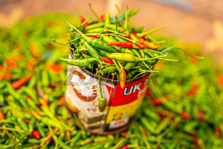 Red and green chili pepper in tin can, local organic market