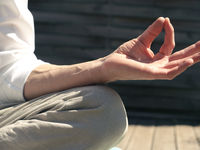 Man relaxes while meditating on a wooden terrace