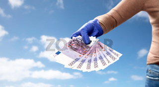 close up of hand in medical glove with money