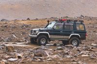 Japanese SUV Toyota Land Cruiser Prado driving on rocky mountain road on background volcanic landscape. Active vacation, off-road trip in gloomy rainy weather