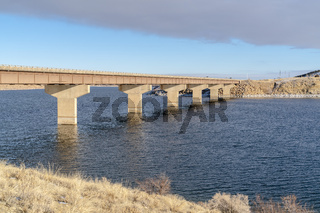 Bridge across blue lake with views of snow covered hills and cloudy blue sky