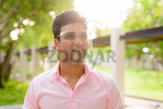 Happy young handsome Indian businessman with face shield thinking at the park