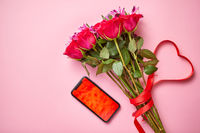 Pink roses bouquet with hart shaped bow and mobile phone with copy space screen