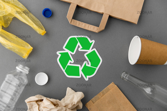 green recycle symbol with household waste on grey