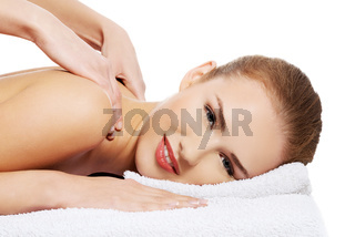 Young beautiful caucasian woman lying on a massage table and is being massaged.