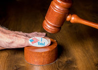 I voted campaign button or sticker on hand with a gavel and mallet to illustrate lawsuits about voting