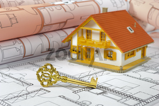 Modellhaus auf Bauplan mit goldenem Schlüssel