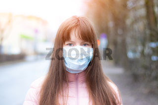 A young girl in a medical mask on the street . Respiratory protection. Coronavirus. Dangerous disease. Article about coronavirus and its treatment.