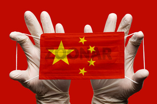 Doctor holding in gloves protection medical face mask, respiratory bandage with China national country flag superimposed on mask. Concept on red background