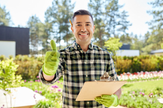 man with clipboard showing thumbs up at garden
