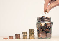 Stacked money coins in the form of a staircase to a jar filled with money coins, hand of a man puts a money coin in the jar