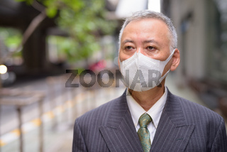 Face of mature Japanese businessman with mask thinking in the city