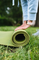 Close-up of woman folding roll fitness after working out in the park
