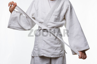Stages of correct tying of the belt by a teenager on a sports kimono, step nine