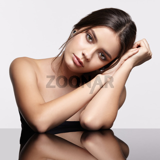 Portrait of young beautiful woman at reflecting table on gray background