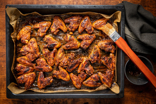 Grilled chicken wings in barbecue sauce in baking tray.