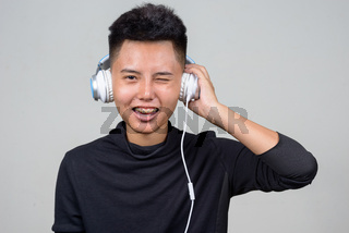 Face of happy young Asian lesbian woman listening to music