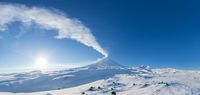 Winter volcanic landscape, panoramic view of eruption active volcano plume gas, ash from crater in sunny day with blue sky
