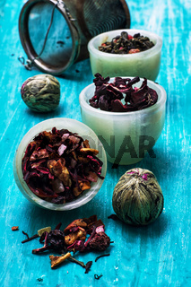 variety of dry tea leaves in jade stacks on wooden background