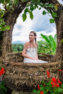 Young woman posing while sitting in the nest on the background of the jungle