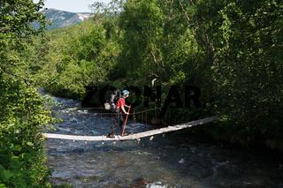Hiker with backpack behind her shoulders crossing mountain river on suspension bridge