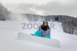 Junge Frau mit Snowboard sitzend im Schnee am Berg